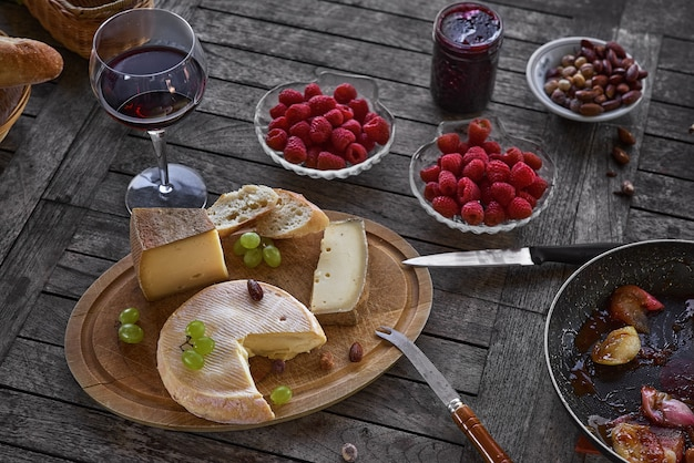 Ассорти из сыров на деревянном подносе с вином, на столе, на домашней террасе, днем нет людей
