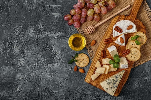 Ассортимент сыра с медом, орехами и виноградом на разделочной доске, вид сверху
