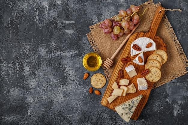 Ассорти из сыров с медом, орехами и виноградом на разделочную доску.