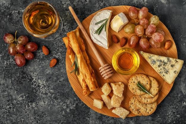 まな板の上にワイン、蜂蜜、ナッツ、ブドウとチーズの品揃え、上面図。