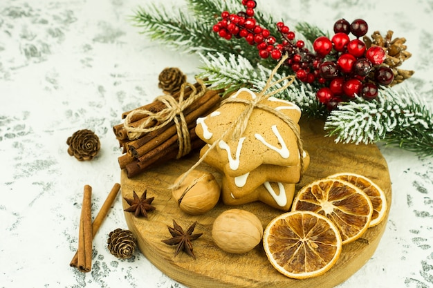 나무 책상에 크리스마스 향신료와 구운 gignerbread 쿠키의 구색. 축제 새 해 인사말 카드입니다.
