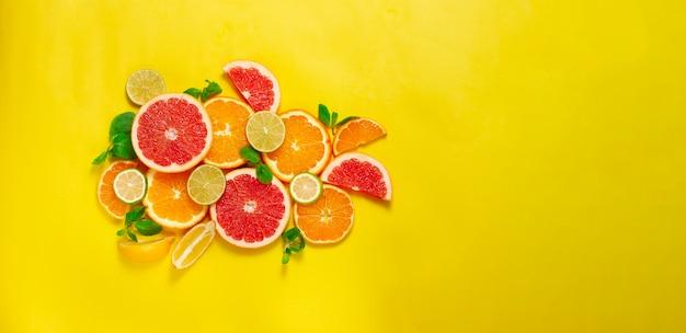 柑橘系の果物の品揃え、黄色の背景、人なし、水平