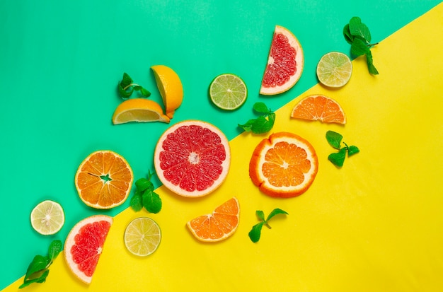 柑橘系の果物の品揃え、黄緑色の背景、人なし、水平