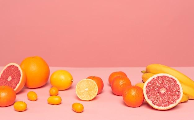 Ассортимент цитрусовых на розовом столе