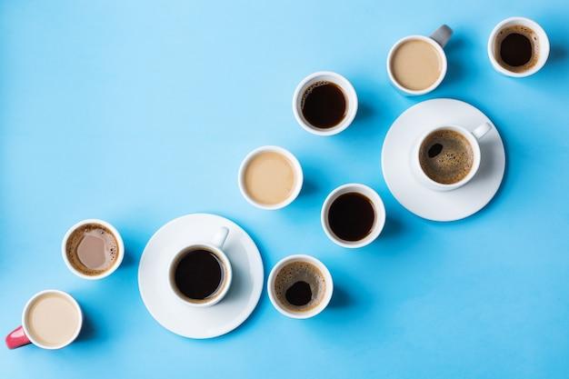 Ассортимент кофейных чашек и кружек с черной обжаркой, американо, капучино, молоком на синем фоне. креативная модная квартира с копией пространства