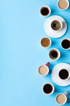파란색 배경에 검정 볶은 아메리카노, 카푸치노, 우유를 넣은 다양한 커피 컵과 머그. 크리에이 티브 트렌디한 복사 공간 플랫 레이