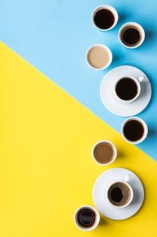 노란색과 파란색 배경에 검은색 로스팅, 아메리카노, 카푸치노, 우유가 있는 다양한 커피 컵과 머그. 크리에이 티브 트렌디한 복사 공간 플랫 레이