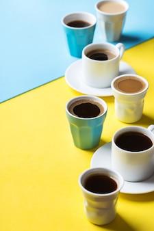 노란색과 파란색 배경에 검은색 로스팅, 아메리카노, 카푸치노, 우유가 있는 다양한 커피 컵과 머그. 창조적 인 유행 복사 공간