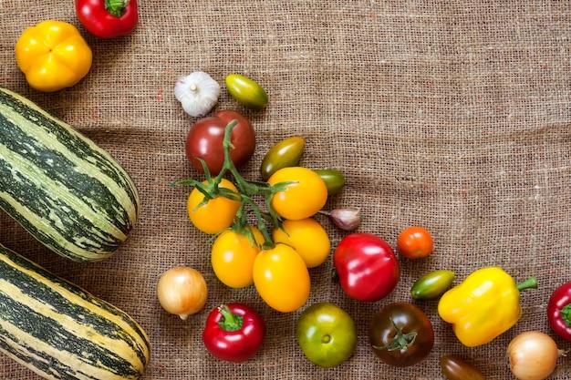 荒布を背景に色とりどりの新鮮な野菜の品揃え。フラットレイ、上面図。スペースをコピーします。
