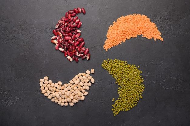 カラフルなマメ科植物レンズ豆豆ひよこ豆の品揃えは暗い表面の上面図でマッシュ