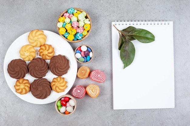 Ассортимент печенья, конфет и мармелад рядом белая доска и листья на мраморном фоне. фото высокого качества