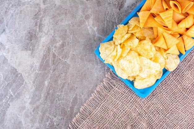 Ассортимент хрустящих чипсов на мраморной поверхности. фото высокого качества