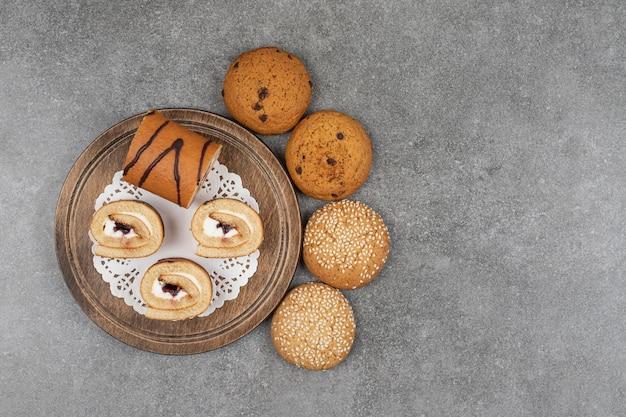 大理石の表面に美味しいロールケーキとクッキーの品揃え