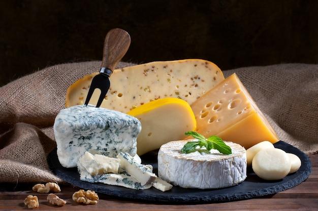 木製の背景にさまざまな種類のチーズの品揃え。チーズの背景。