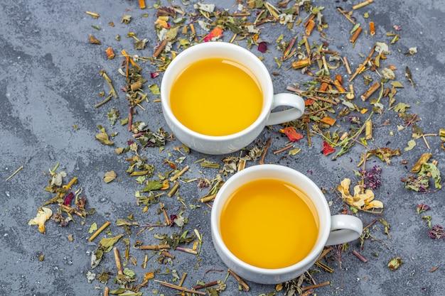 さまざまな乾燥茶葉と2杯の緑茶の品揃え。オーガニックハーブ、グリーンアジアティー、ドライフラワーペタル、ティーセレモニー用。