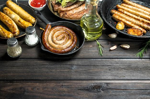 Ассортимент различных жареных колбас с соусами на деревенском столе.