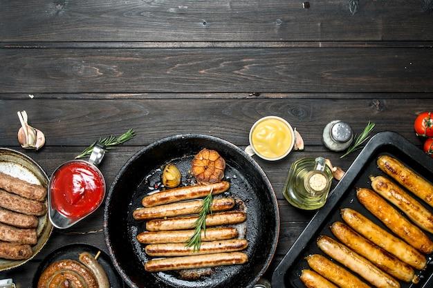 Ассортимент различных жареных колбас с соусами на деревянном столе.