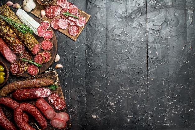 黒の素朴なテーブルにスパイスとハーブを添えたさまざまなサラミの品揃え。