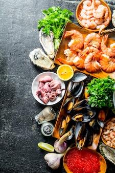 Ассортимент различных морепродуктов с чесноком, зеленью и специями. на темном деревенском фоне