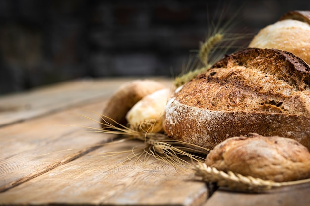 빵집의 나무 탁자에 있는 호밀과 밀가루로 만든 다양한 종류의 빵. ƒâ ã,â¡ 복사 공간