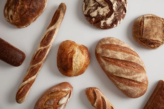 다양한 종류의 빵, 덩어리, 바게트, 밀, 누룩에 호밀 유기농 밀가루로 만든 흰색 표면에 격리. 빵집 및 건강 식품 개념. 천연 생물학적 제품.