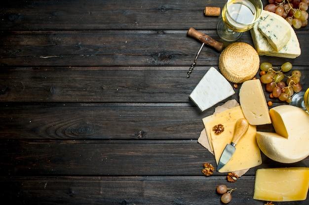 素朴なテーブルにブドウと白ワインを添えたさまざまな種類のチーズの品揃え。