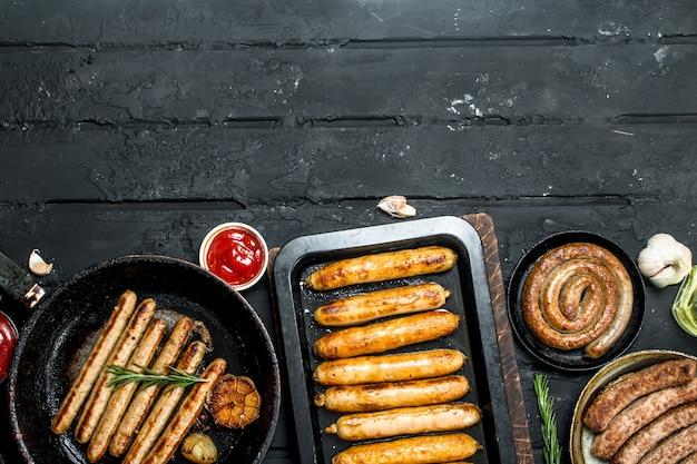 Ассорти из разных видов жареных колбас. на черном деревенском фоне.