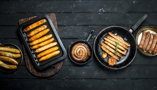 黒の素朴なテーブルにさまざまな種類の揚げソーセージの品揃え。