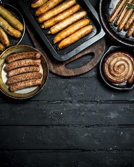 Ассорти из разных видов жареных колбас. на черном деревенском столе.