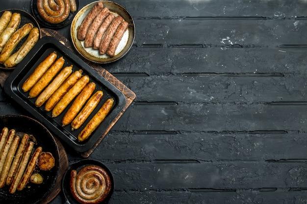 黒い木製のテーブルにさまざまな種類の揚げソーセージの品揃え。