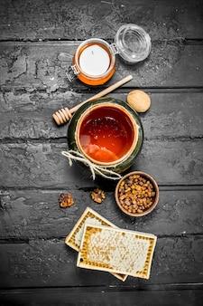 さまざまな種類の蜂蜜の品揃え。黒の素朴なテーブルの上。