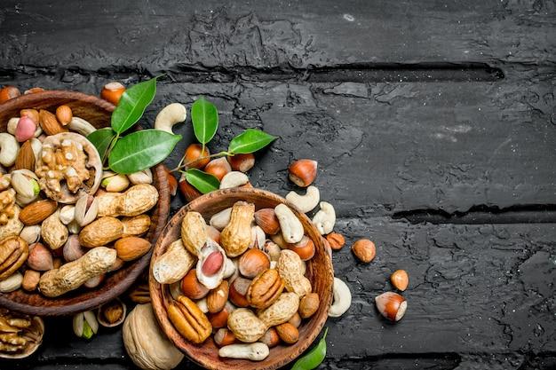 ボウルにさまざまな種類のナッツの品揃え。黒の素朴な背景に。