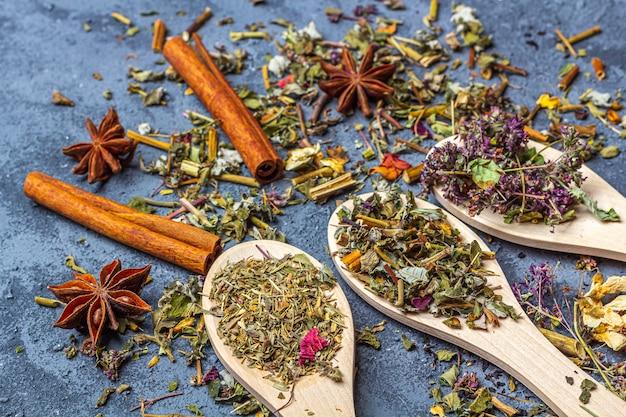 素朴なスタイルの木製のスプーンで別のお茶と生姜、アニス、シナモンの品揃え。茶道のための乾燥した花びらが付いている有機性ハーブ、緑および紅茶。フラットレイアウト、コピースペース