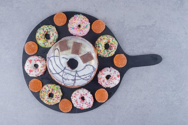 Ассортимент пончиков и мармеладов на черном подносе на мраморной поверхности