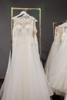 Ассортимент платьев, висящих на вешалке на фоне студии