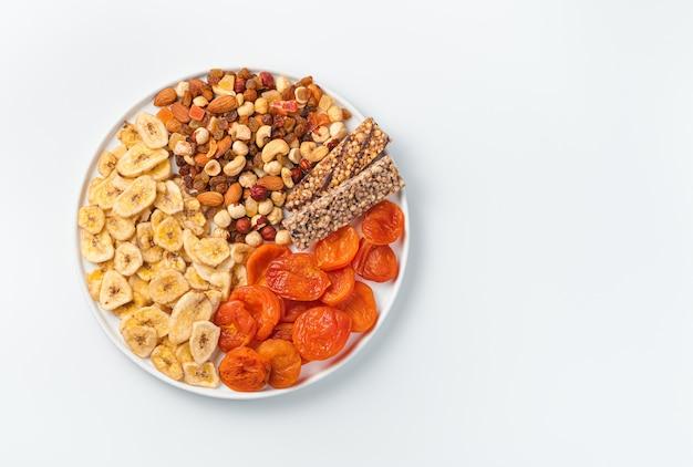 Ассортимент сухофруктов, орехов и батончика мюсли в плоской белой тарелке на светлой стене. вид сверху с копией пространства. натуральные, полезные закуски.