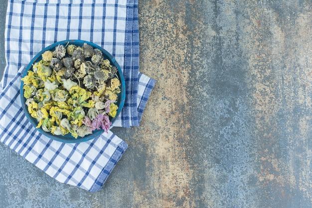 Ассортимент сушеных органических цветов на синей тарелке.