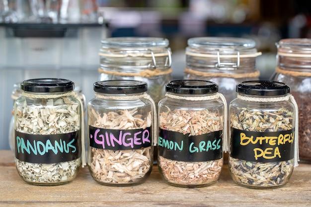 Ассортимент сушеных специй в стеклянных бутылках на деревянных фоне. сухой имбирь, пандан, лимонная трава и горох-бабочка в стеклянных банках, крупным планом