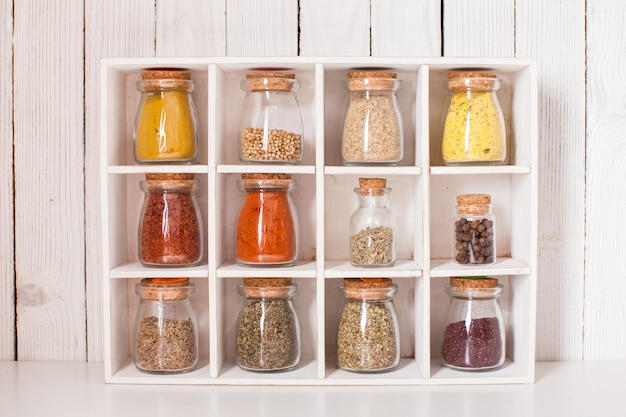 나무 상자에 있는 빈티지 유리병에 있는 다양한 건조 향신료