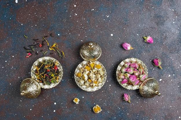 Ассортимент сухого чая в золотых винтажных мини тарелках. фон видов чая