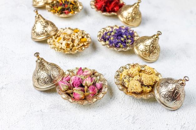 黄金のヴィンテージミニプレートでの乾燥茶の品揃え。お茶の種類の背景