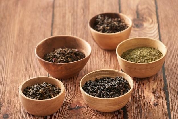 Ассортимент сухого чая в белых мисках на деревянной поверхности