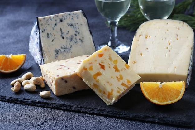 어두운 배경에 슬레이트 보드에 엘리트 치즈의 구색. 와인 파티를 위한 간식. 확대
