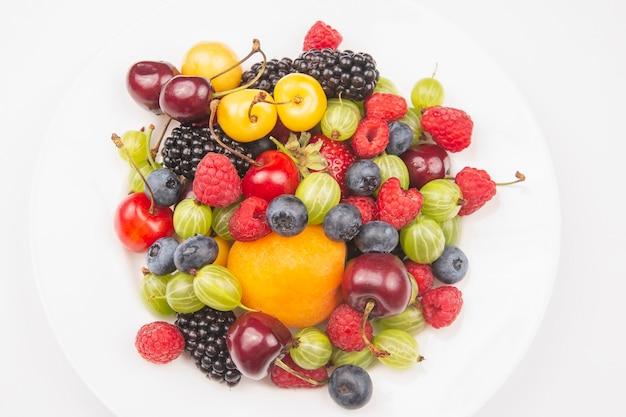 하얀 접시에 신선한 딸기의 구색입니다. 유용한 비타민 건강 식품 과일. 건강한 야채 아침 식사