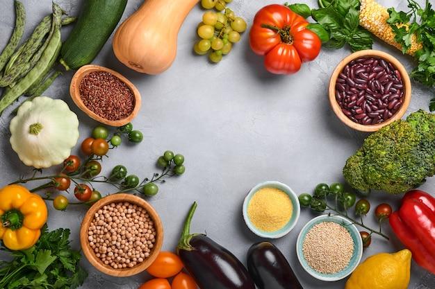 Ассортимент свежих фруктов и органических разноцветных радужных овощей на сером фоне бетона. приготовление пищи и фон здоровой чистой пищи и макет.