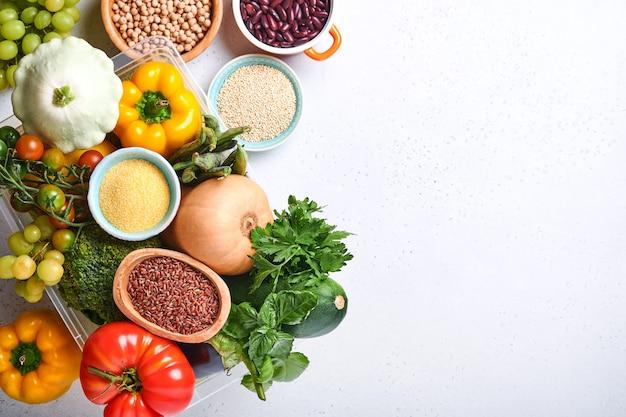 灰色のコンクリートの背景に新鮮な果物と有機色とりどりの虹色の野菜の品揃え。料理と健康的なきれいな料理の背景とモックアップ。