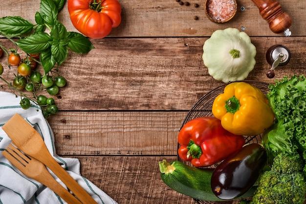 Ассортимент свежих фруктов и органических разноцветных радужных овощей на старом деревянном деревенском фоне. еда приготовления фона и макет.