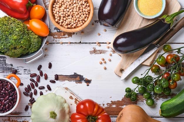오래된 나무 배경에 있는 다양한 신선한 과일, 콩, 시리얼, 유기농 여러 가지 빛깔의 무지개 야채. 음식 요리와 건강한 깨끗한 음식 배경과 조롱.