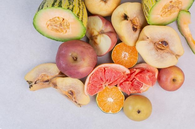 Ассортимент свежих фруктов на белом столе.