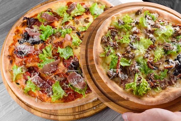 햄, 살라미 소시지, 고기, 토마토, 샐러드, 치즈와 나무 테이블에 나무 보드에 신선한 이탈리아 피자의 구색.